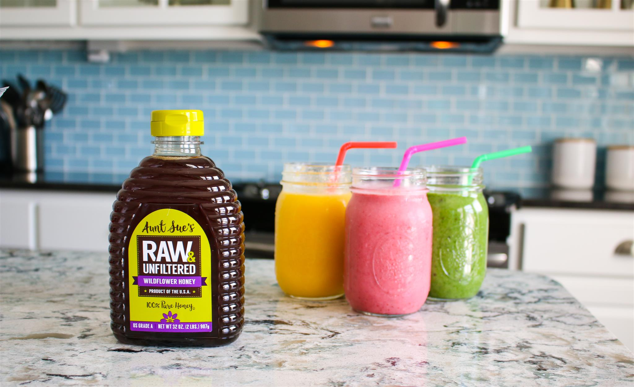 Aunt Sue's Raw & Unfiltered Honey with Fruit Smoothies on Counter
